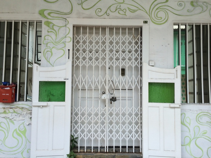 The pintu pagar (half-doors for ventilation and privacy) are visible along some of the shophouses