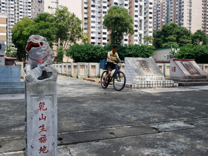 A cyclist on his way through the cemetery. Also present is the symbol of a stone lion, a common protector of Chinese graves.