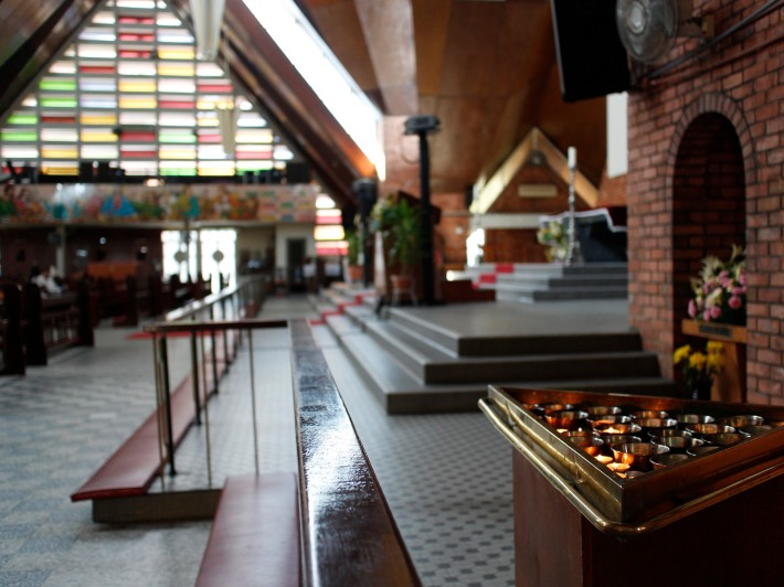 A side view of the altar with the multicoloured glass panels in the background