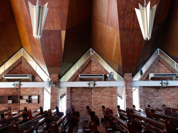 Inside the church, brick walls align symmetrically to the cruciform design of the main hall.