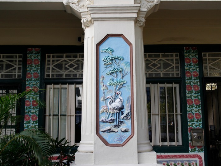 The stucco plasterwork of a crane in the outlying column of the shophouse