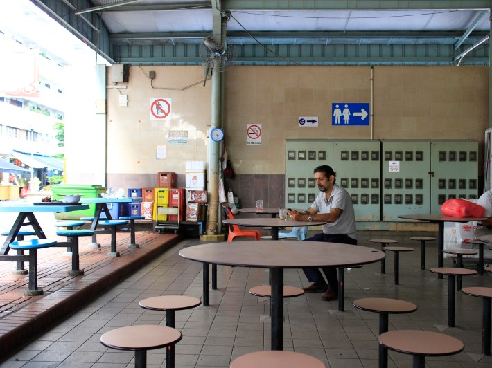 A man sits at the Ghim Moh Market & Food Centre, a hallmark of the estate  that is quiet on weekdays but thronged by many locals on weekends.