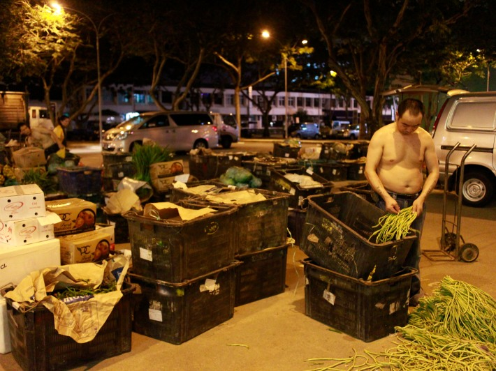 A hawker weeds out any bad goods that might affect the quality of produce