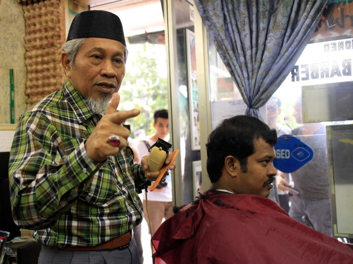 Mr Kamsari Gari,63, a long-time resident and owner of Jali Jali Malay Barber entertaining questions from the crowd