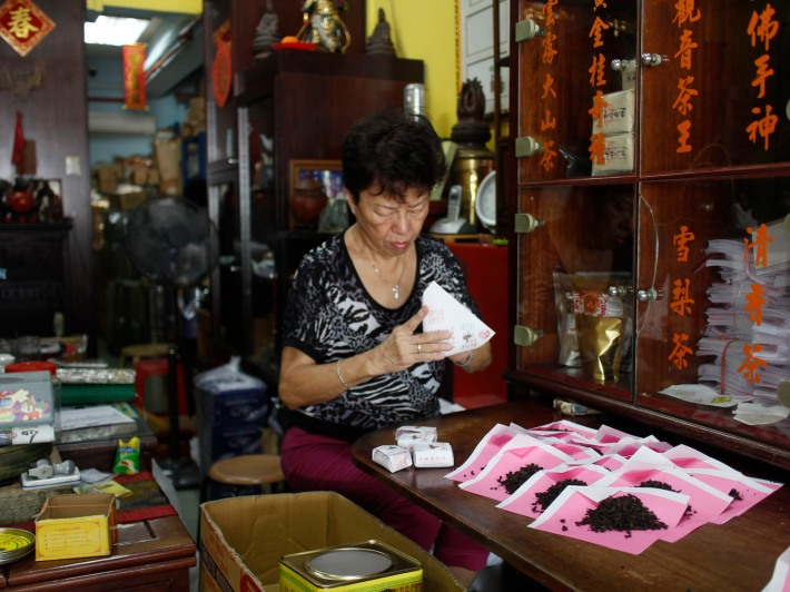 Pek Sin Choon is very much a traditional family business, here one of the family members is packing oolong tea leaves in the traditional pink packaging common in many medical halls as well.