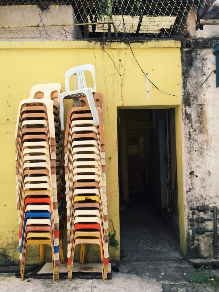 A colourful assortment of plastic chairs kept high and dry till nighttime
