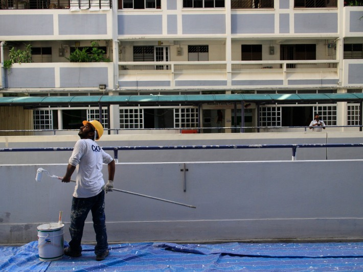 A worker works on the new lime green coating that will replace the identifiable light blue coat of the Hong Lim Apartments