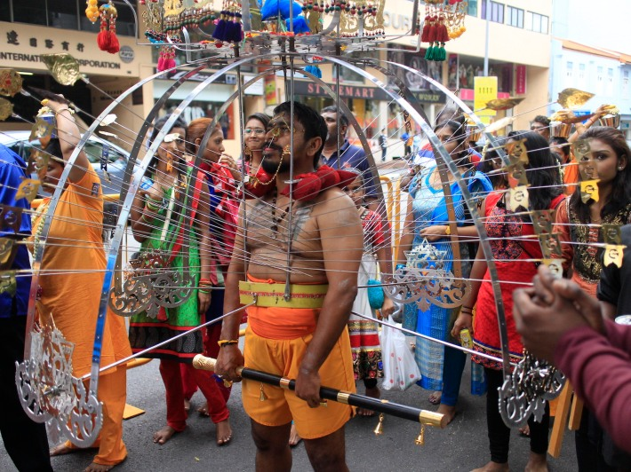 A kavadi bearer waiting patiently along the crowded streets at Thaipusam