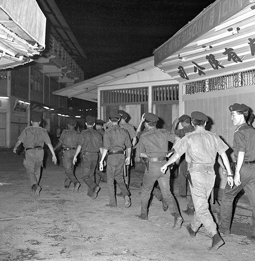 Officers from the Old Beach Road Police Station enter Gay World Stadium in response of a Barisan Socialis screening of 'Aid to Vietnam'. Image from Singapore Press Holdings.