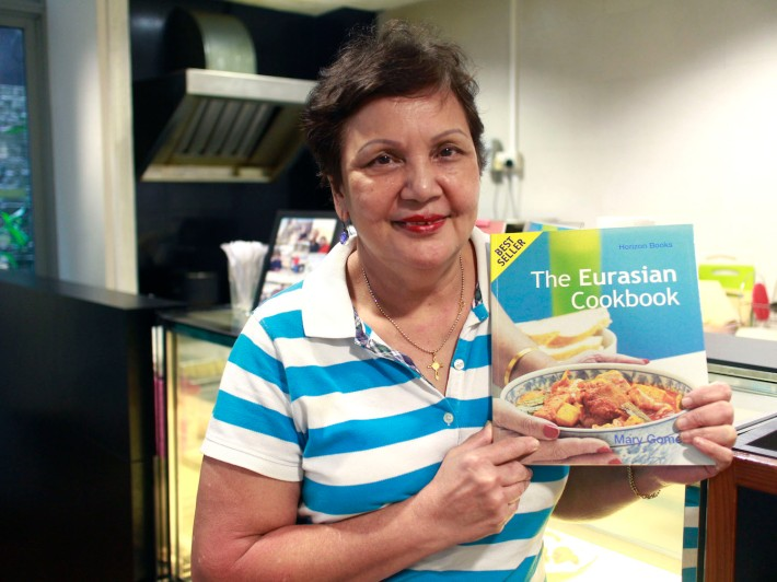 Mary Gomes with the 2001 edition of 'The Eurasian Cookbook', the first-ever Eurasian Cookbook produced in Singapore