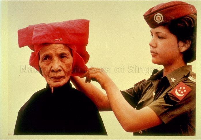 A samsui woman receiving help before heading out for a celebratory march-past at the 1980 National Day Parade. Image courtesy of The National Archives of Singapore.