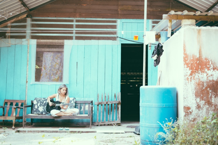 The 27-year old singer-songwriter reflects outside her neon blue kampong house she called home for four full-months.